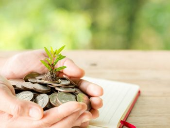 The woman's hand is holding many coins, the green natural background